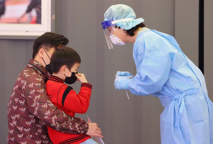 A medical worker tries to take test samples for COVID-19 at a makeshift testing center near Seoul Station in central Seoul, April 25. Yonhap