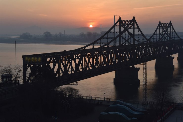The sun rises behind the Sino-Korea Friendship Bridge, which spans the Yalu River between China and North Korea, as seen from the Chinese city of Dandong in this Feb. 22, 2019 photo. AFP-Yonhap