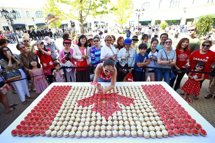A crowd watches Cera Rivers apply icing to the last of 512 cupcakes that make up a Canadian flag during Canada Day celebrations on July 1, 2017 in Richmond, British Columbia. Richmond is the most ethnically Chinese city in the world outside Asia, and home to large numbers of Hong Kong and mainland Chinese immigrants. AFP
