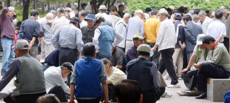 A group of people, mostly elderly, crowds a corner of Jongno 3-ga road in Seoul's Jongno District. Korea Times file