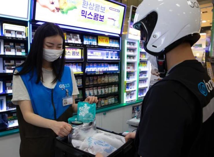 In this July 2020 file photo, a convenience store clerk, left, puts superabsorbent polymer-based icepacks inside a package to be delivered. Korea Times file
