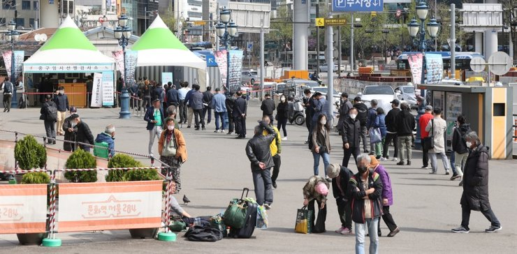 People stand in line at a makeshift COVID-19 testing center in front of Seoul Station, Friday. Yonhap