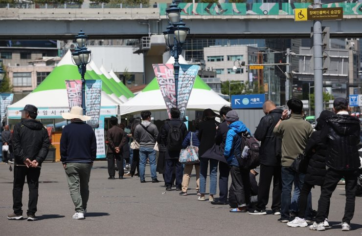 People stand in line to get COVID-19 tests at a makeshift testing center in front of Seoul Station, Wednesday, the day after Korea's daily new coronavirus cases rose to 731, the largest number in 97 days. Yonhap