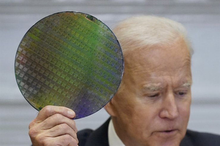 US President Joe Biden holds up a silicon wafer as he participates in the virtual CEO Summit on Semiconductor and Supply Chain Resilience in the Roosevelt Room of the White House, April 12 in Washington. AP-Yonhap