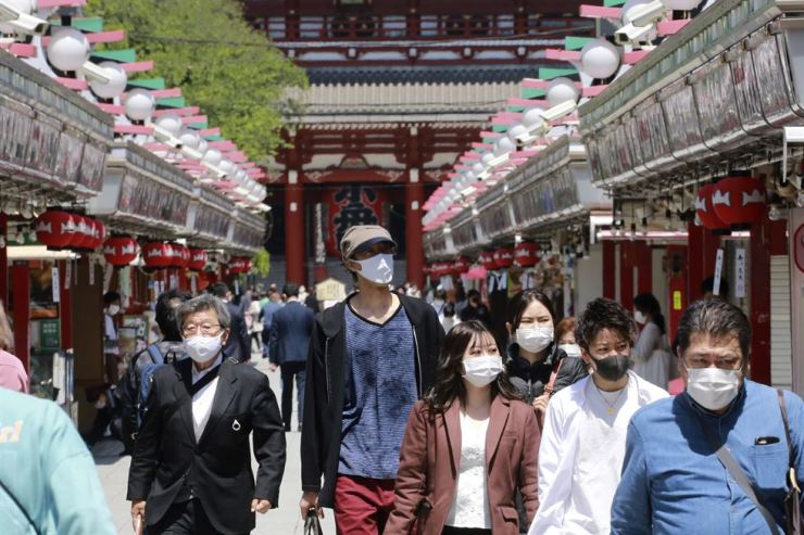 People wearing face masks to protect against the spread of the coronavirus stroll at Asakusa district in Tokyo, Monday. AP-Yonhap