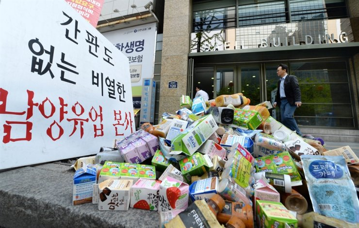 Namyang's dairy products thrown in a pile outside the company's headquarters in Seoul in May 2013, after it was hit for forcing subcontractors to purchase products nearing expiration dates. Korea times file.