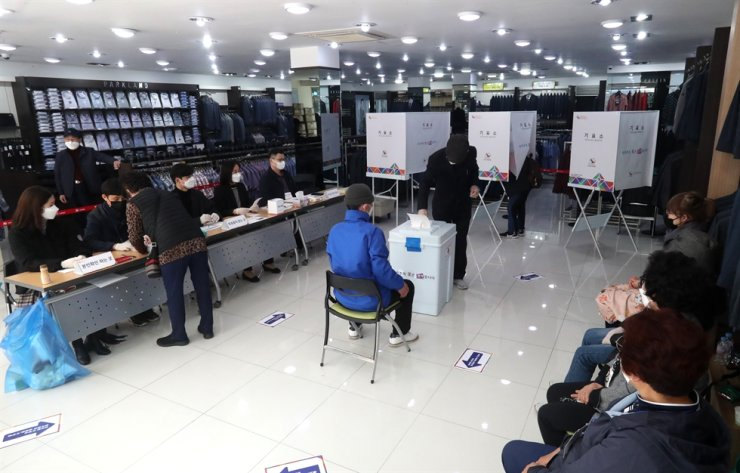 Citizens vote for Busan mayor at a polling station set up inside a clothing store in the Jung District of the city, Wednesday. Yonhap