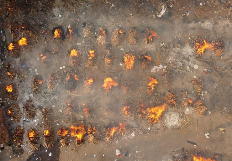 A mass cremation of people, who died due to COVID-19, is seen at a crematorium ground in New Delhi, April 28. Reuters-Yonhap
