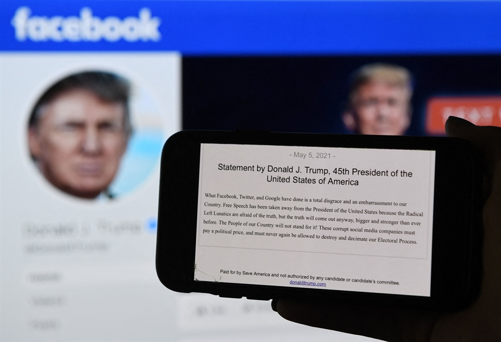 In this file photo illustration, a phone screen displays a Facebook logo with the official portrait of former US President Donald Trump on the background, on May 4, 2021, in Arlington, Virginia. AFP-Yonhap