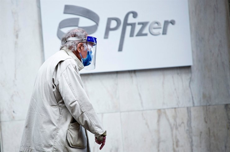 In this file photo taken on March 11, a man wearing facemask and shield walks past the Pfizer headquarters in New York one year after the pandemic was officially declared. AFP-Yonhap