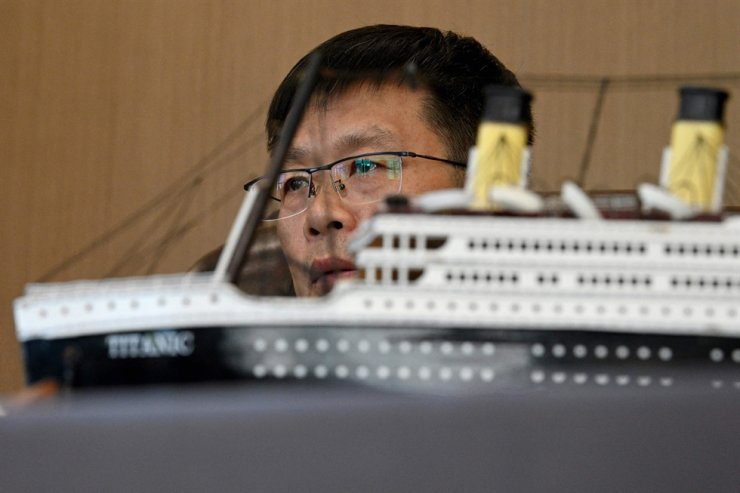 This April 26 file photo shows Su Shaojun, an investor helping to build a life-size replica of the Titanic, next to a model of the ship during an interview at his office in Daying County in China's southwest Sichuan province. AFP-Yonhap