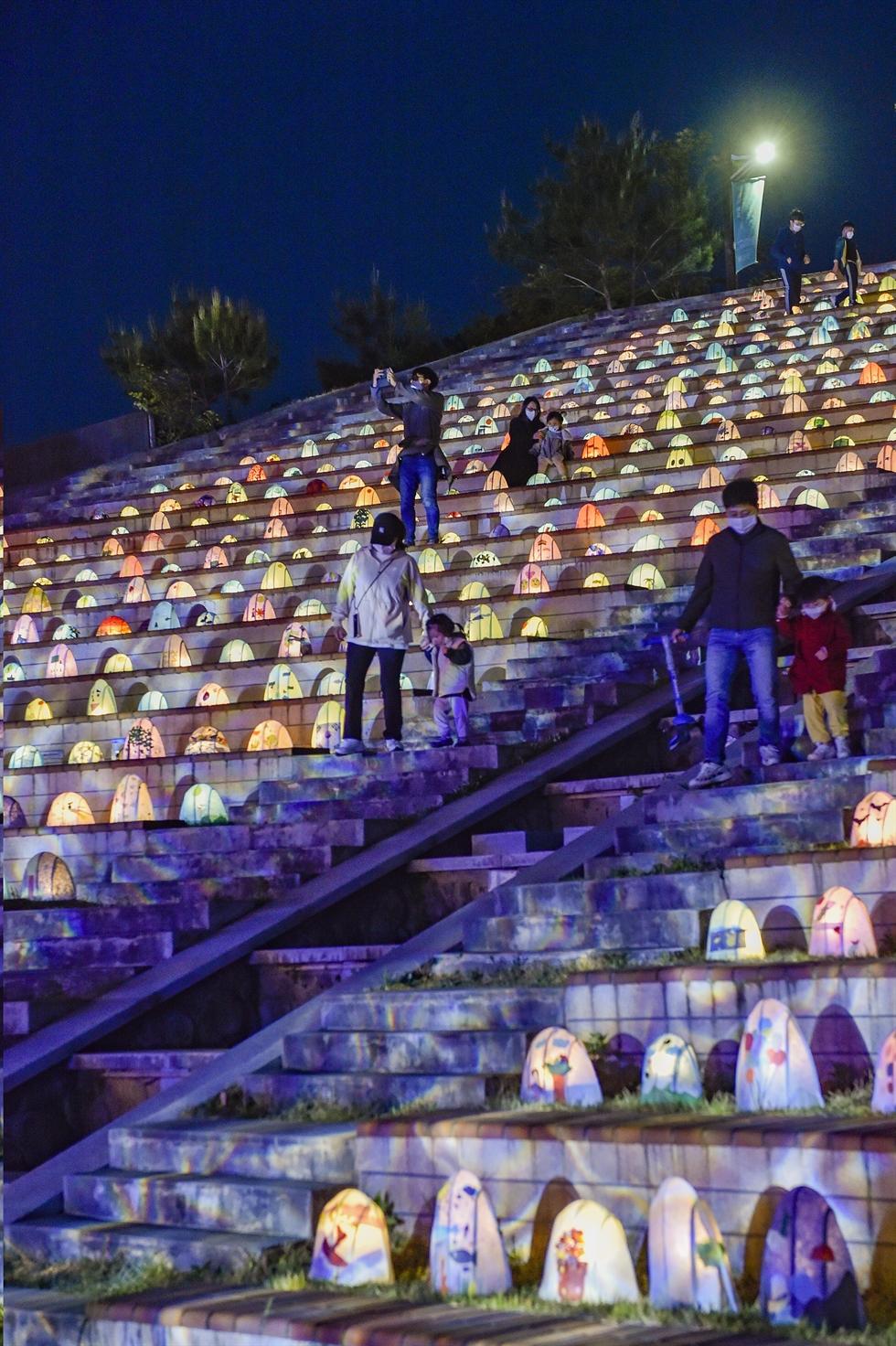 Visitors walk down stairs decorated with various hanji lanterns at
