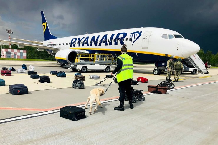 In this May 23 file photo, a Belarusian dog handler checks luggage bags off a Ryanair Boeing 737-8AS parked on Minsk International Airport's apron in Minsk. AFP-Yonhap