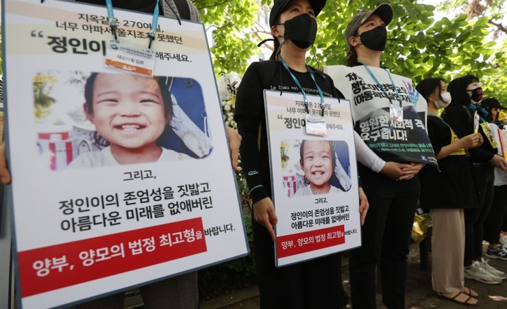 Protesters hold signs demanding heavy punishment for the woman indicted on charges of abusing her adopted daughter to death, outside the Seoul Southern District Court, Friday. The court sentenced the mother to life in prison. Yonhap