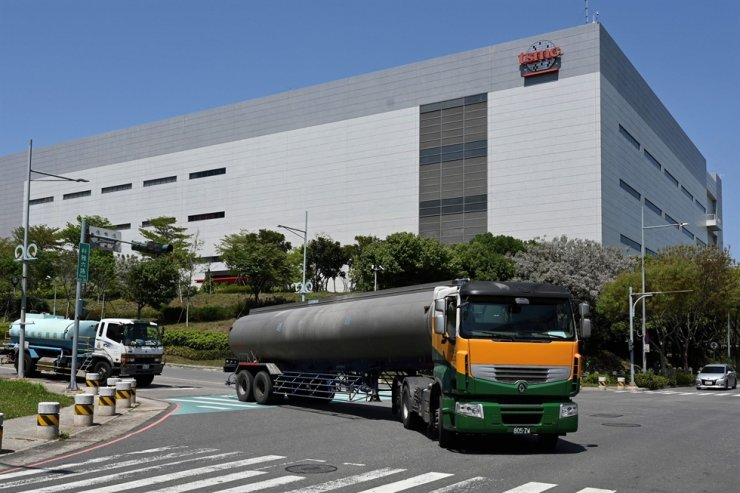 This photo taken on Mar. 25 shows two water trucks passing a TSMC factory in Taichung, central Taiwan. AFP-Yonhap