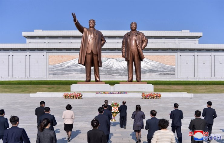 North Koreans pay tribute to the statues of North Korea founder Kim Il-sung, left, and his son and successor Kim Jong-il in this photo released by the North's Korea Central News Agency, April 26. Yonhap