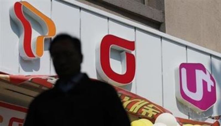 A person walks by a mobile phone dealership in this file photo. Yonhap