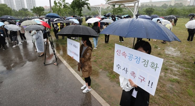 People hold signs at a rally held at the Banpo Han River Park, southern Seoul, Sunday, calling for thorough police investigation to uncover the truth about the death of a college student who went missing April 25 and whose body was found in the Han River five days later,. Yonhap