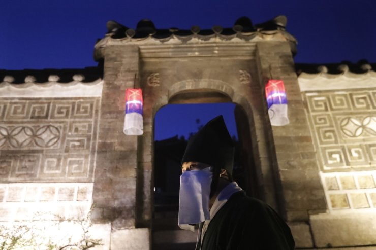 An employee waits for arrival of visitors during a Moonlight Tour amid the coronavirus pandemic at Changdeokgung Palace in Seoul, May 13. AP-Yonhap