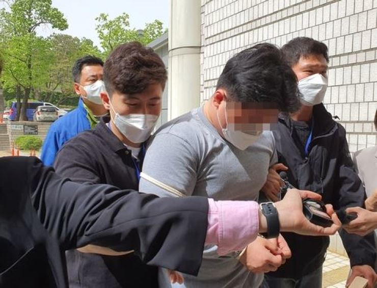 A man in his 20s accused of brutally assaulting a cab driver in his 60s is being taken to the Seoul Central District Court, May 7. Yonhap