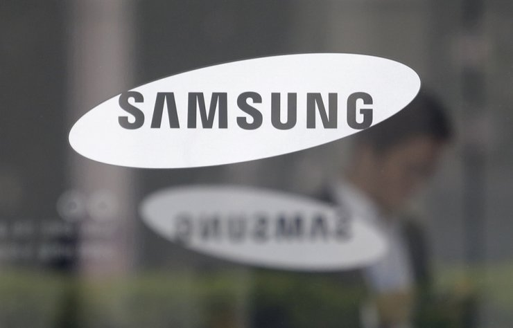 In this file photo, an employee walks past a logo of the Samsung Electronics at its office in Seoul. AP-Yonhap
