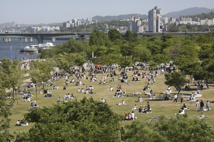 People wearing face masks as a precaution against the coronavirus relax at a public park along the Han River in Seoul, May 9. AP-Yonhap