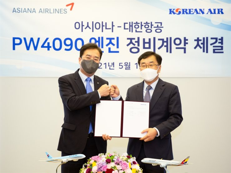 Lee Soo-keun, Korean Air executive VP COO, left, and Jin Jong-seob, Asiana Airlines executive VP of strategic planning, pose after signing an engine maintenance deal at Asiana Airlines' headquarters in Seoul, Wednesday. Courtesy of Korean Air