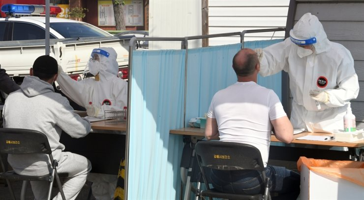 Medical workers take test samples for COVID-19 at a makeshift testing center in Gangneung, Gangwon Province, May 3. More than 40 foreign migrant workers in the east coast city tested positive for COVID-19 after preemptive coronavirus testing, municipal officials said Tuesday. Yonhap