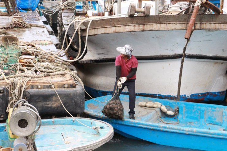 A migrant worker work on a fishing boat at a port in North Jeolla Province. Korea Times file