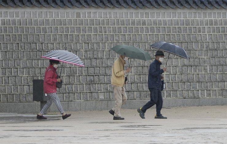 Visitors wearing face masks as a precaution against COVID-19 walk in the rain at Gyeongbok Palace in Seoul, May 28. AP-Yonhap