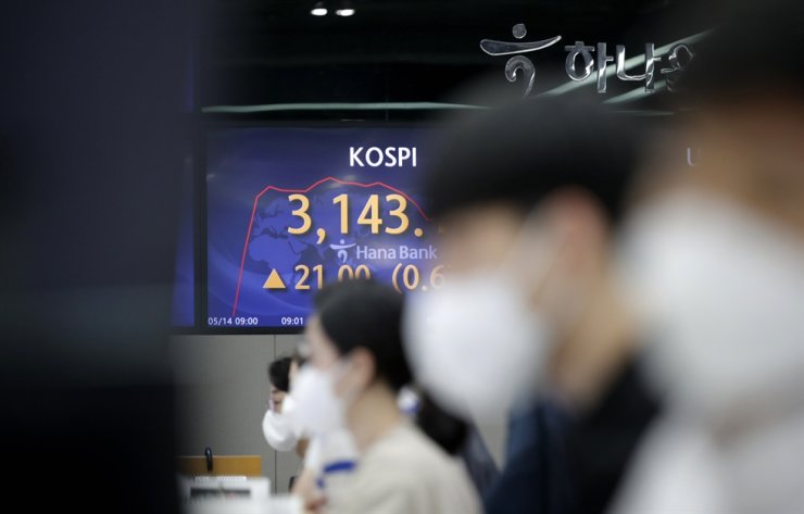 A currency trader watch computer monitors near the screen showing the Korea Composite Stock Price Index at the foreign exchange dealing room in Seoul, May 14. AP-Yonhap