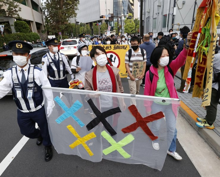 People protest against holding the Tokyo 2020 Olympics amid the COVID-19 pandemic, around Olympic Stadium (National Stadium) as an Olympic test event for athletics is held inside the venue in Tokyo, May 9. Reuters-Yonhap