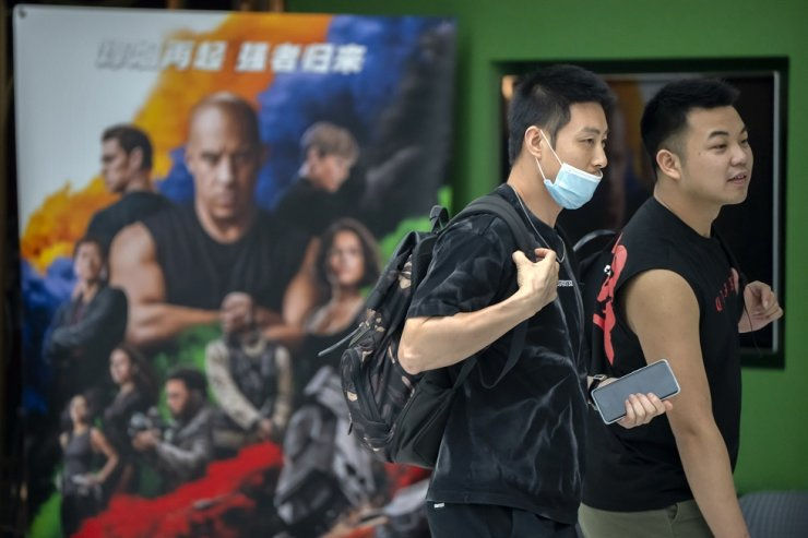 People walk past a poster for the movie 'Fast & Furious 9' at a shopping mall in Beijing, May 26. WWE star and actor John Cena apologized after calling Taiwan a country in promotional interviews for his upcoming film 'Fast & Furious 9.' AP-Yonhap