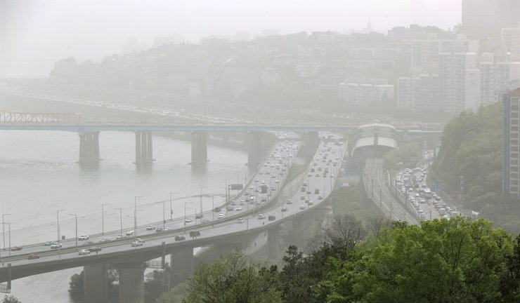 Atmosphere around Gangbyeonbukro Highway next to Han River in Seoul is foggy with clouds of fine dust on Friday. Yonhap