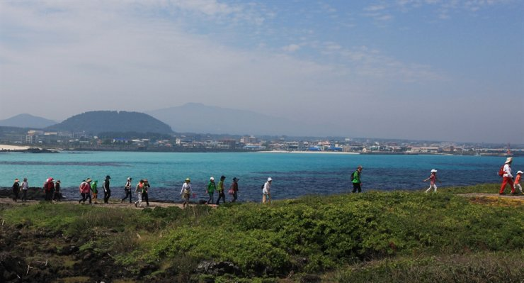 Hikers walk along Route 20 of Jeju Olle Trail near Gimnyeong Beach. Courtesy of the Jeju Olle Foundation
