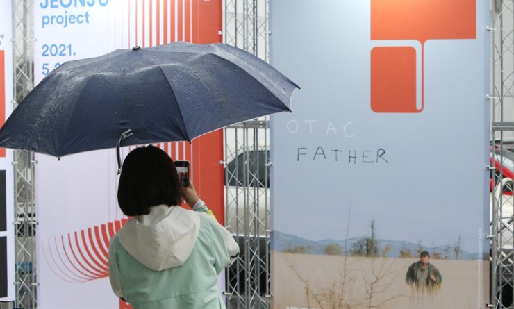 A movie fan takes a photo of the film poster for 'Father,' which was chosen as the 22nd Jeonju International Film Festival's opening film on Jeonju Film Street, Saturday. Yonhap