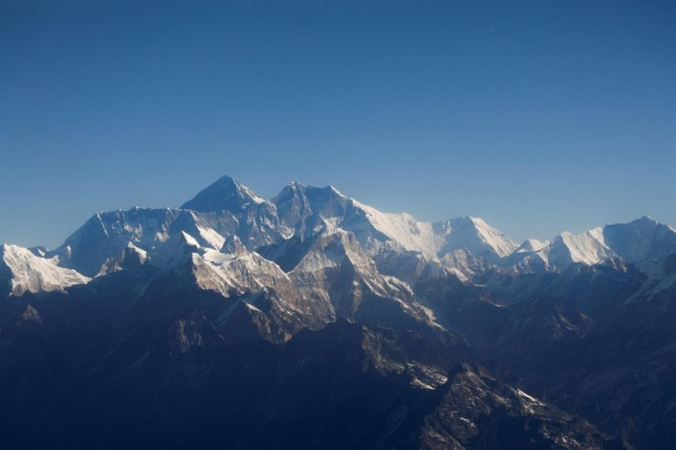 In this Jan. 15, 2020, file photo, Mount Everest, the world highest peak, and other peaks of the Himalayan range are seen through an aircraft window during a mountain flight from Kathmandu, Nepal. Reuters-Yonhap
