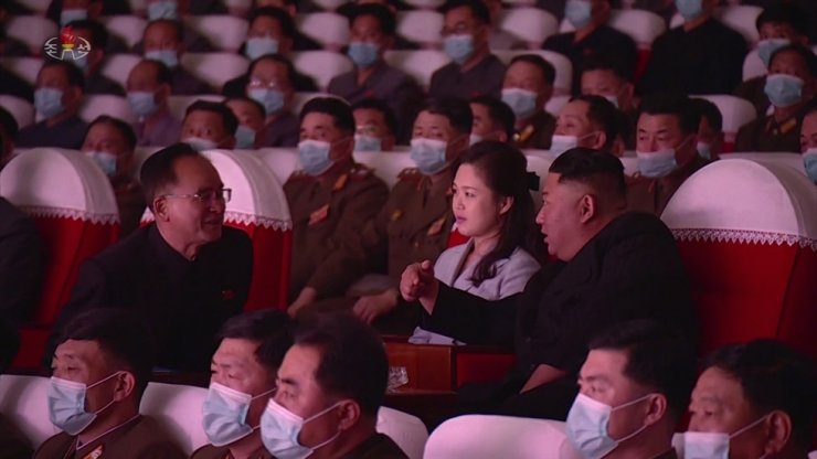 North Korean leader Kim Jong-un, right, speaks to Jo Yong-won, left, secretary for organizational affairs of the central committee of the Workers' Party, during a performance by the art groups of servicemen's families from the Korean People's Army at the Mansudae Art Theatre in Pyongyang, Wednesday. All spectators, excluding Kim, his wife Ri Sol-ju and a handful of high ranking officials, wore face mask while watching the performance. Yonhap