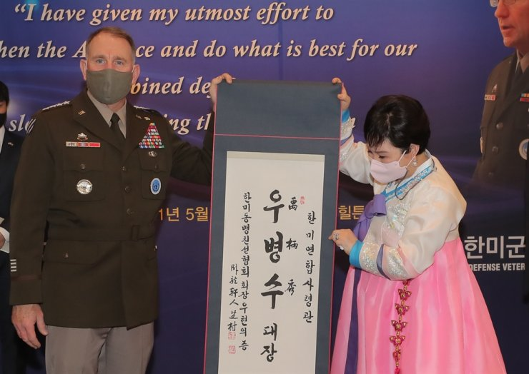 Outgoing U.S. Forces Korea Commander Gen. Robert Abrams, left, receives a Korean name, Woo Byung-soo, as a gift from a South Korea-U.S. friendship group for his 'contribution to the alliance and defense of South Korea' during a farewell event in Seoul, May 13. Yonhap