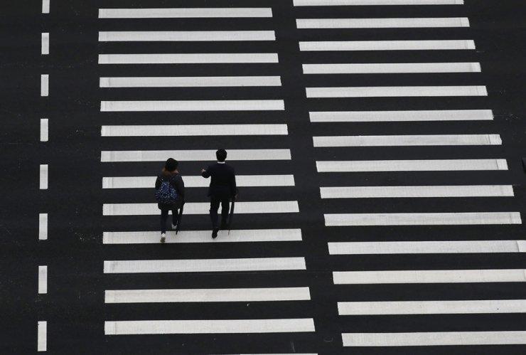 People wearing face masks as a precaution against the coronavirus walk along a crosswalk in Seoul, May 7. AP-Yonhap