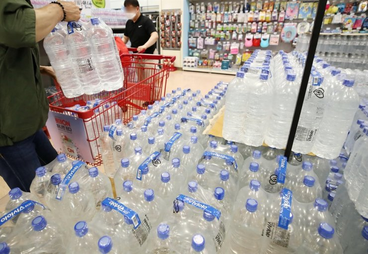 In this July 2020 file photo, cases of label-less bottled water are stacked for sale at a store in Seoul. Making such bottles has been named by the government as one of the top three environmental policies implemented this year. Yonhap