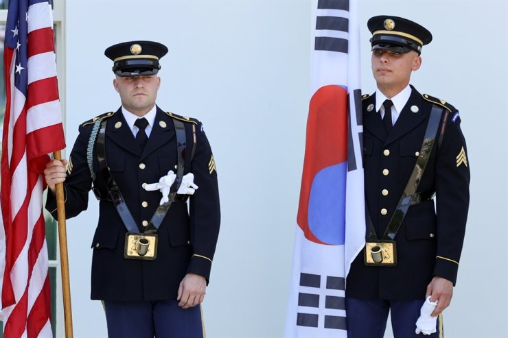 Military honor guard members with U.S. and Korean flags prepare for the arrival of Korea's President Moon Jae-in to meet with U.S. President Joe Biden at the White House in Washington, May 21. A top Cheong Wa Dae official dismissed speculation Tuesday that China may launch another round of economic retaliation against Korea over its summit agreement with the United States that touched on a sensitive regional security issue. Reuters-Yonhap