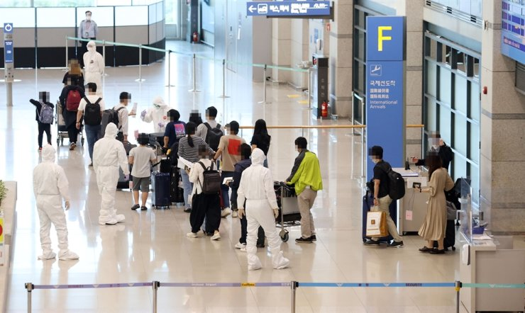 Korean citizens who were flown back home from India via a chartered flight gather in the arrival area at Incheon International Airport, Wednesday. Yonhap