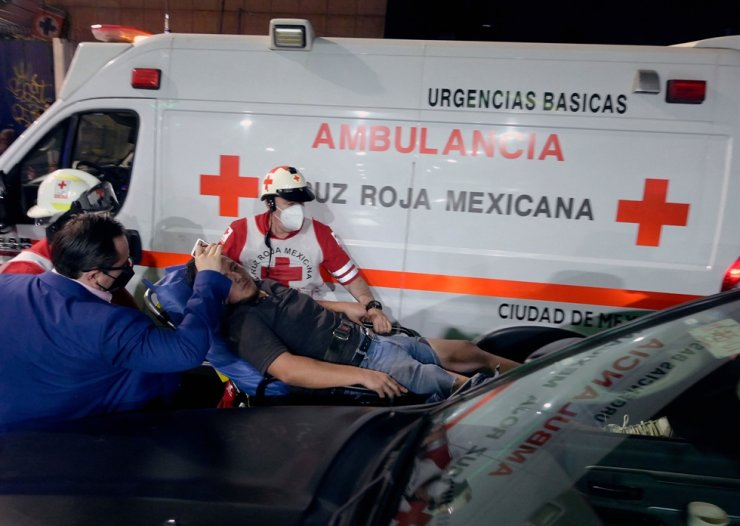 Members of the Mexican Red Cross carry an injured man on a stretcher after an overpass for a metro partially collapsed in Mexico City on May 3. AFP-Yonhap