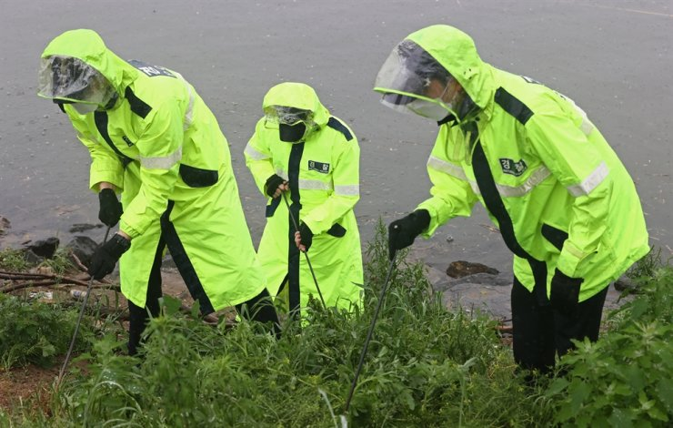 Police officers search for a missing cell phone which belonged Son Jeong-min's friend, at Banpo Han River Park in southern Seoul, Sunday. Yonhap