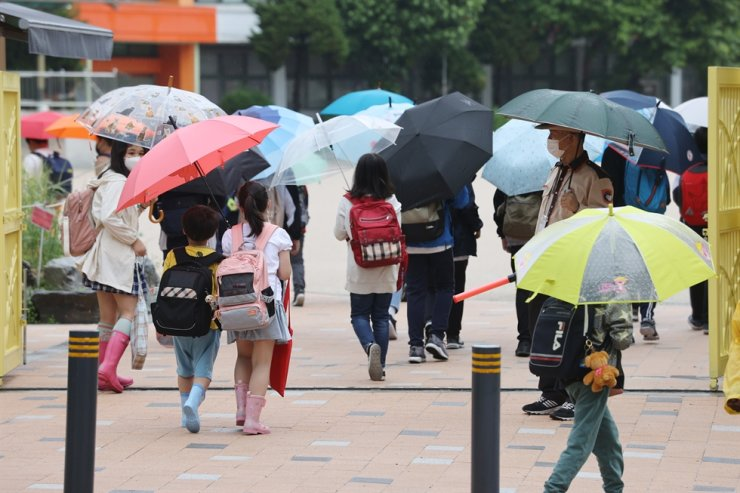 Students arrive at an elementary school in Seoul, Monday. While schools currently offer both in-person and online classes that follow the COVID-19 pandemic social distancing guidelines, the education ministry aims to resume in-person classes fully starting from the second semester. Yonhap