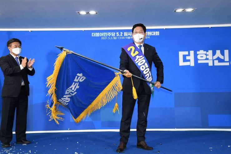 Song Young-gil, a five-term lawmaker of the ruling Democratic Party of Korea, waves the party's flag at its headquarters in Seoul, Sunday, after being elected new leader. He won 35.6 percent of the votes from party members and the public. Yonhap