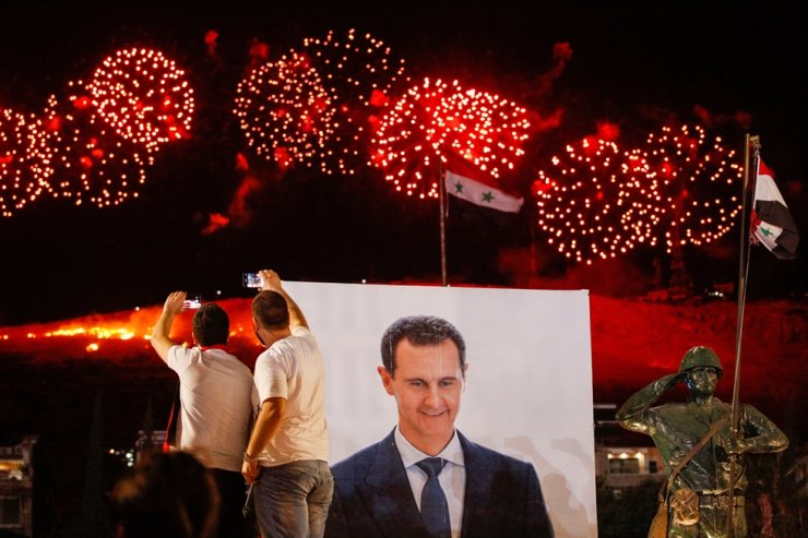 A poster depicting Syria's president Bashar al-Assad is seen as his supporters celebrate after the results of the presidential election announced that he won a fourth term in office, in Damascus, Syria, May 27. Reuters-Yonhap