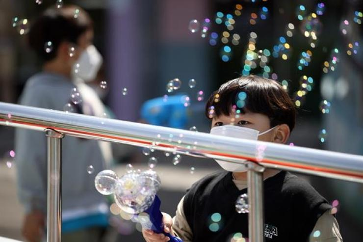 A boy wearing a mask holds a bubble toy at Children's Grand Park, eastern Seoul, May 5 (Children's Day). Yonhap
