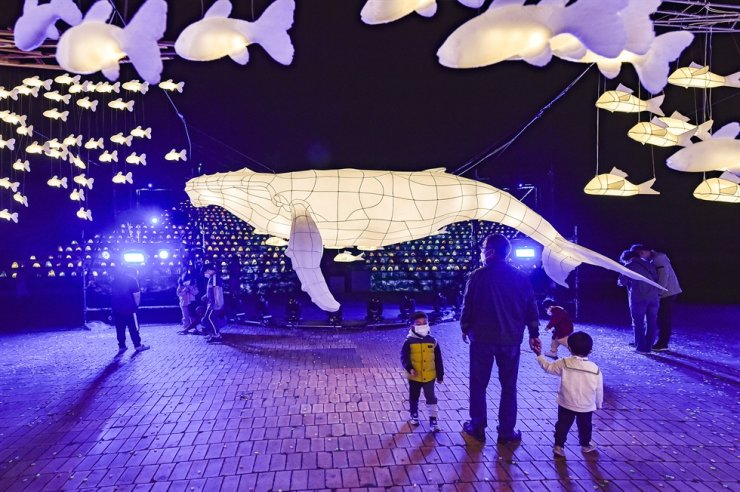 Visitors look at a giant whale hanji lantern at